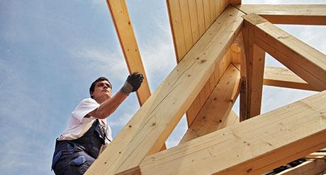 Mann beim Dachdecken mit Holzprofilen, Fasebretter, KVH bzw. BSH