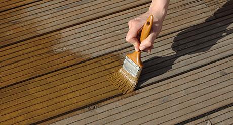 Holzdielen werden mit Holzlasur gestrichen