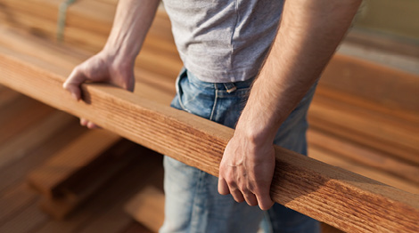 Mann trägt Terrassenholz für die Montage einer neuen Terrasse