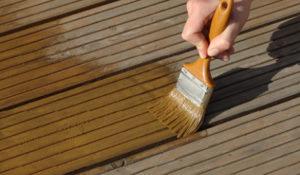 Terrassenreinigung mit Öl und Pinsel